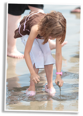 Young girl shifting through the sand with her hands in shallow water.